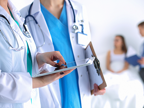 Healthcare professionals relying on network uptime as they analyze patient data on a tablet