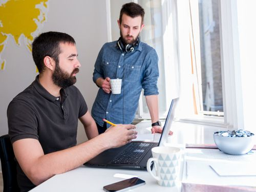Two programmers reviewing work on a laptop